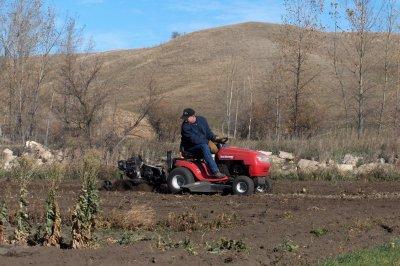 Gary Baker tills ground to prepare it for seeding winter rye.